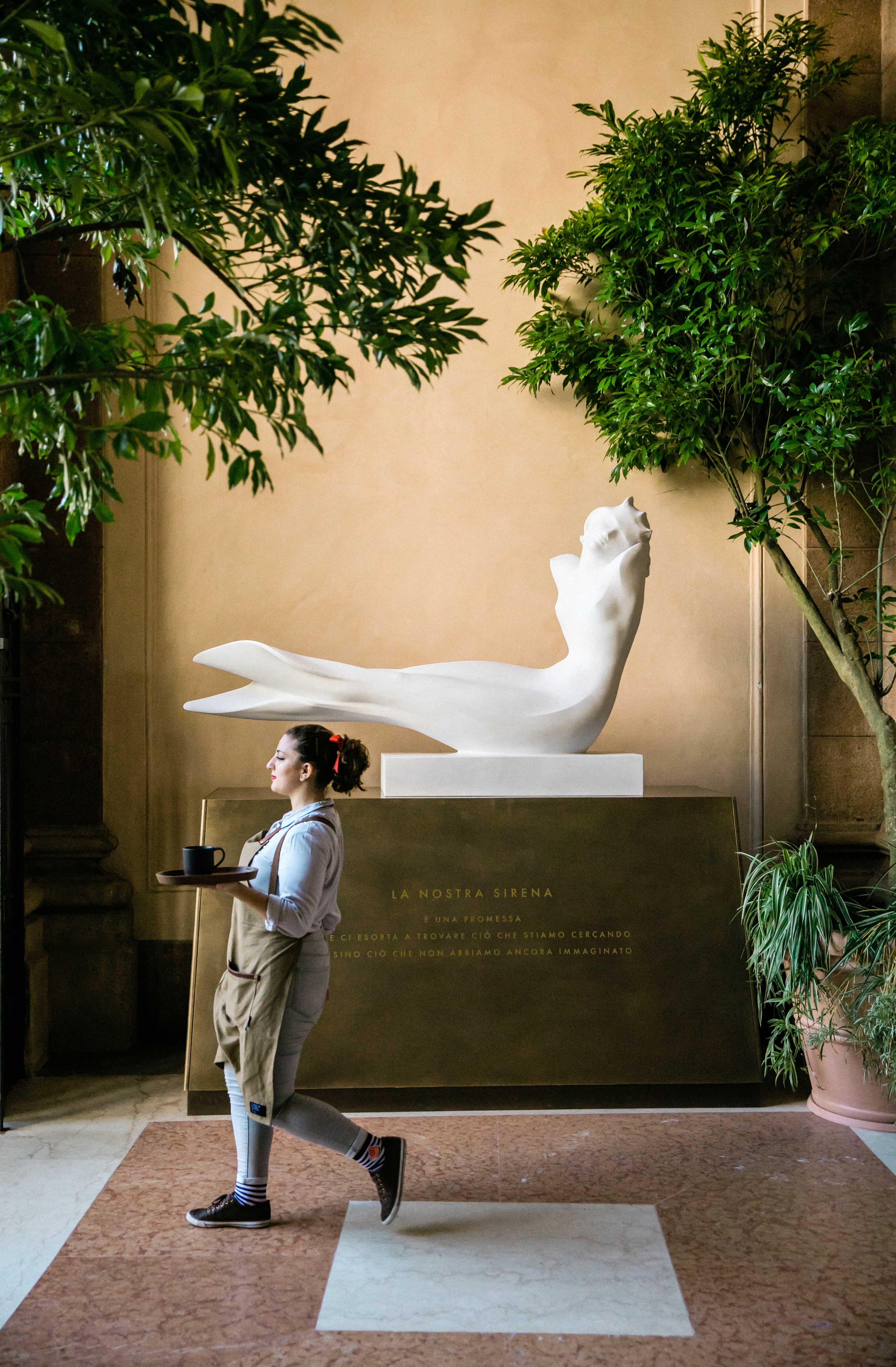 A partners walks past a sculpture of the Starbucks siren at the Starbucks Reserve Roastery in Milan, Italy on Tuesday, September 4, 2018. (Joshua Trujillo, Starbucks)