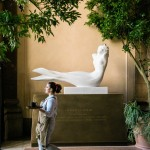 A partners walks past a sculpture of the Starbucks siren at the Starbucks Reserve Roastery in Milan, Italy on Tuesday, September 4, 2018. (Joshua Trujillo, Starbucks)
